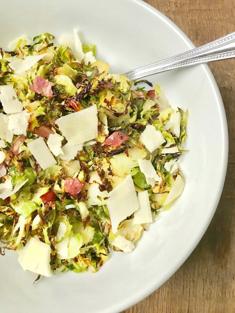 A large white serving bowl with a silver spoon on a wooden surface. In the bowl is 21 day fix crispy shaved brussels sprouts topped with diced turkey bacon, shaved parmesan cheese, and a balsamic vinegar reduction.