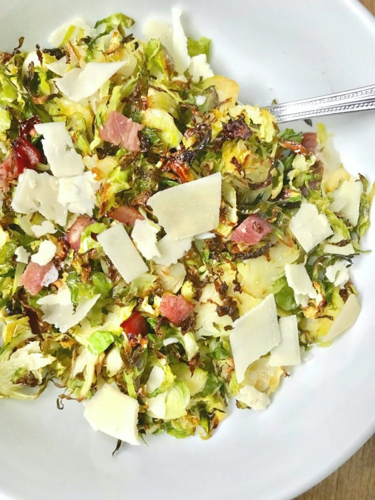 Close up of a large white serving bowl with a silver spoon on a wooden surface. In the bowl is 21 day fix crispy shaved brussels sprouts topped with diced turkey bacon, shaved parmesan cheese, and a balsamic vinegar reduction.