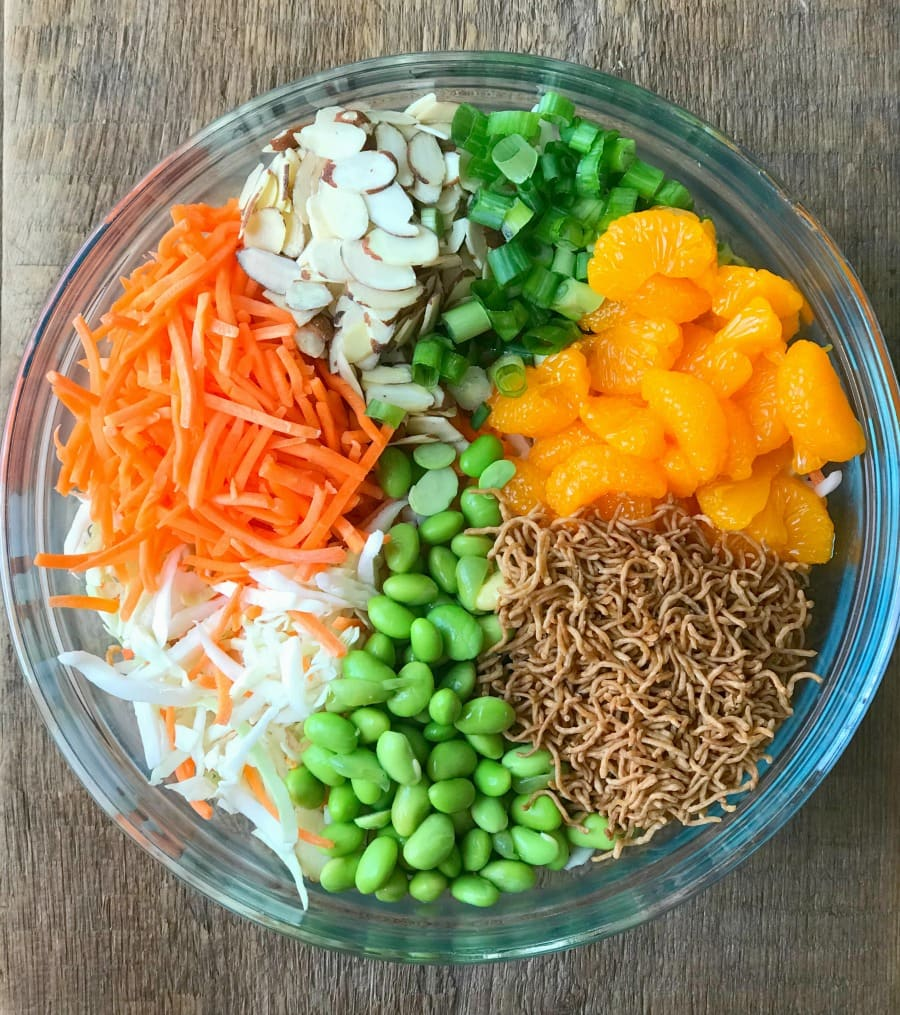 Glass bowl filled with Salad- Cabbage, Carrots, Almond, Green Onions, Mandarin Oranges, and toasted brown rice ramen noodles.