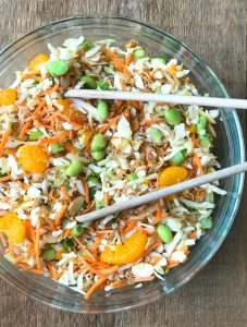 Ramen Noodle Salad in a Glass Bowl with Wooden tongs