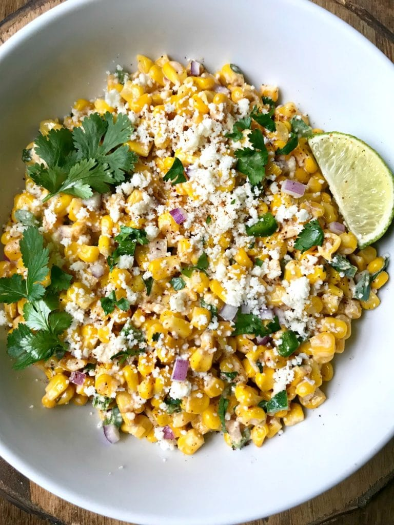 A white bowl filled with Mexican street corn salad topped with cotija cheese and cilantro with a lime wedge on the side