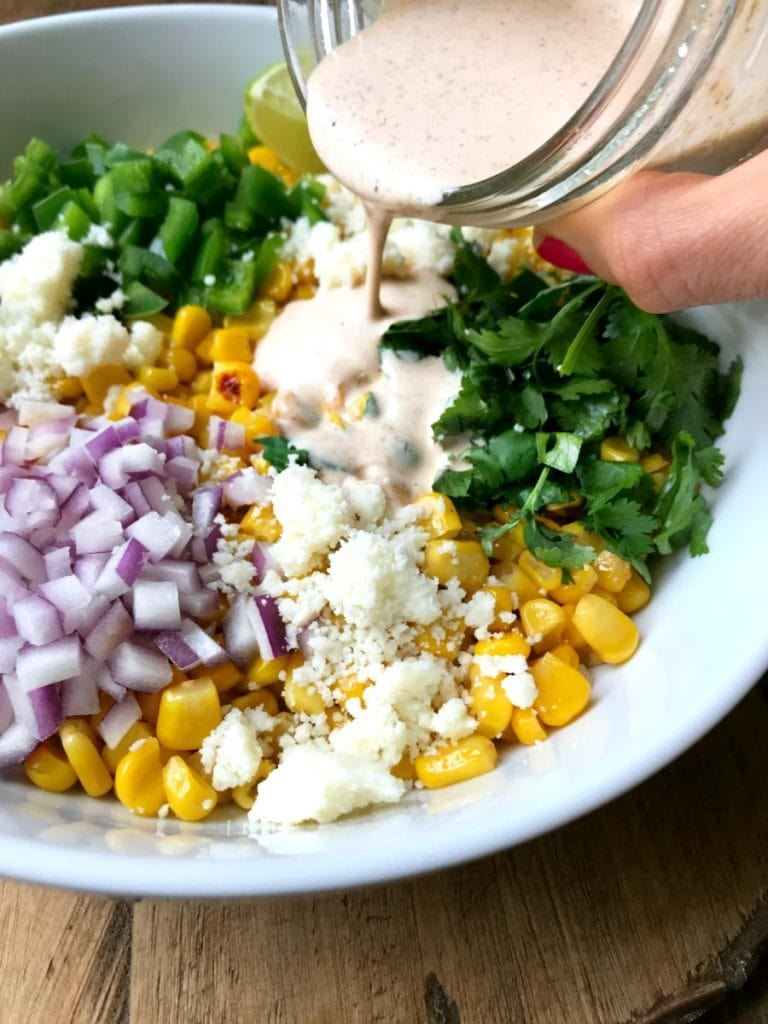 A white bowl containing corn, red onion, pepper, cotija cheese, lime, and cilantro- the ingredients for mexican street corn salad- on a wooden surface