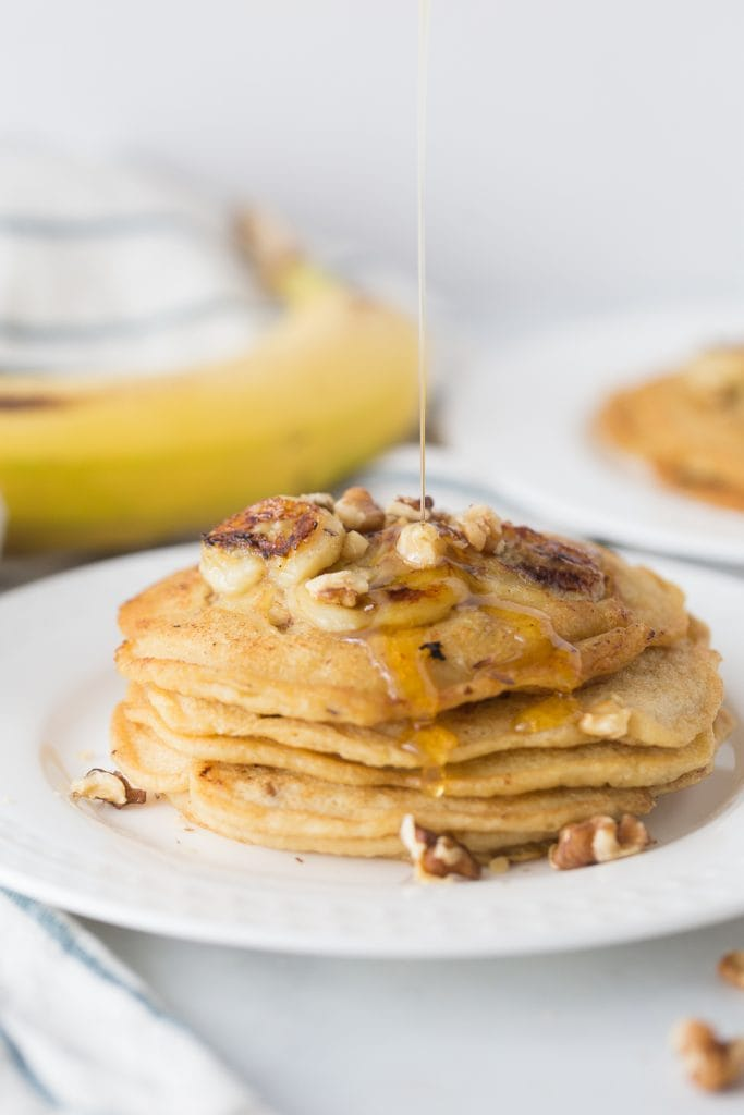 A stack of Gluten Free pancakes with caramelized bananas and walnuts on top and on the side. There is syrup drizzling on the stack from above, out of frame.