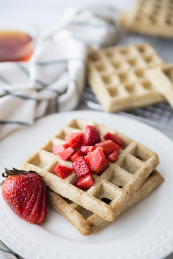 Two square homemade waffles on a white plate topped with diced strawberries and a sliced strawberry for garnish.