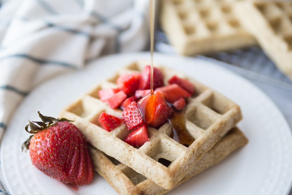Two square homemade waffles on a white plate topped with diced strawberries and a sliced strawberry for garnish.  Maple syrup is being drizzled from above.