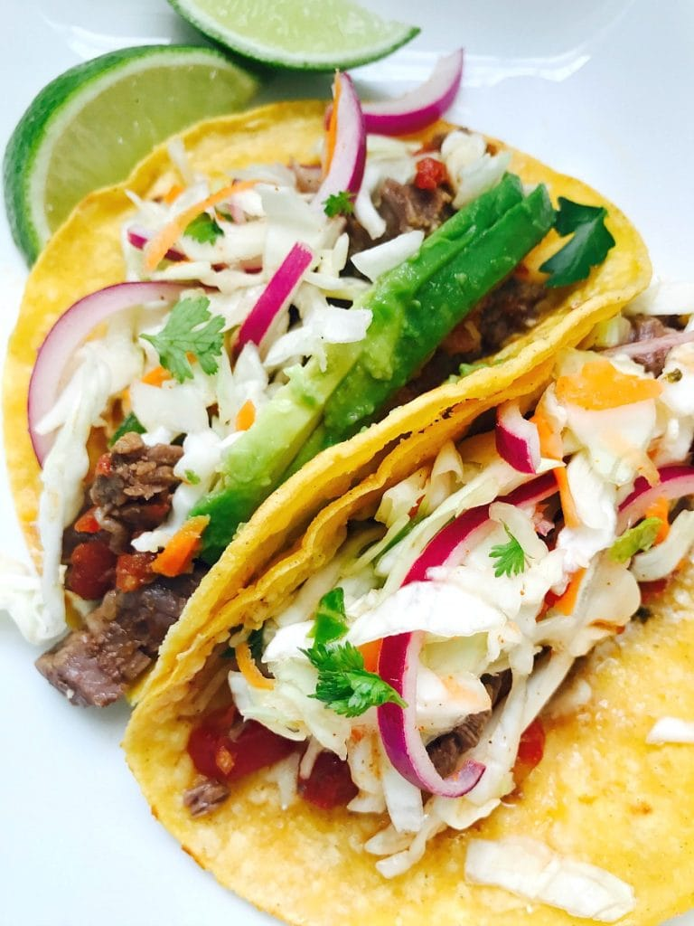 Two flank steak tacos are topped with red onion, cole slaw, yogurt dressing, and avocado with lime wedges on the side