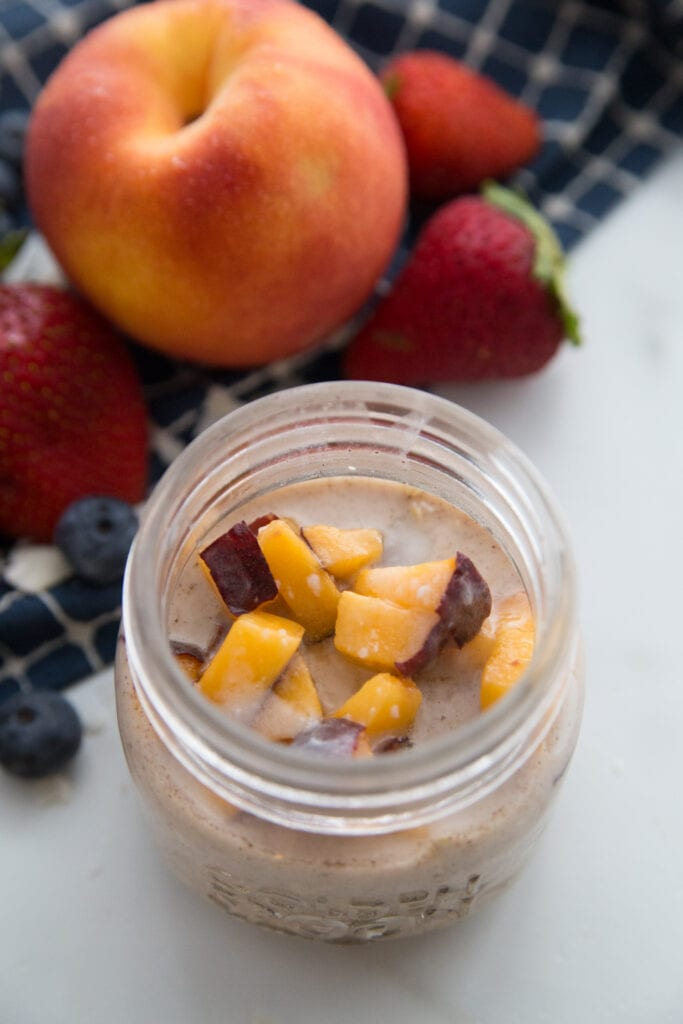 A jar of peaches and cream overnight oats sitting next to a large peach and some strawberries