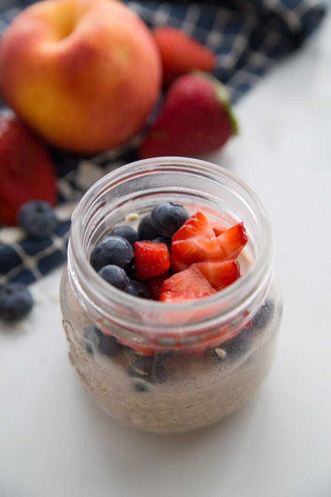 A jar of very berry overnight oats topped with blueberries and strawberries