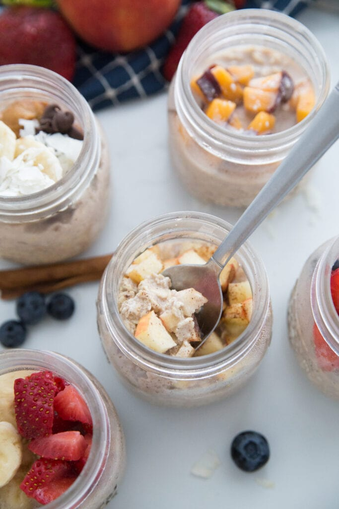 Overnight Oats in Mason Jars with 5 different toppings. The apple cinnamon one has a spoon inside.