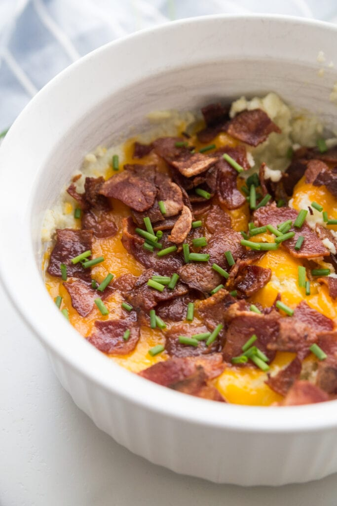 A white Instant Pot safe casserole dish topped with bacon, cheddar, and chives.