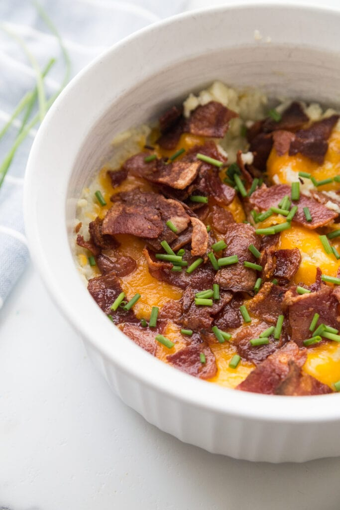 A white Instant Pot safe casserole dish with Mashed Cauliflower topped with bacon, cheddar, and chives.