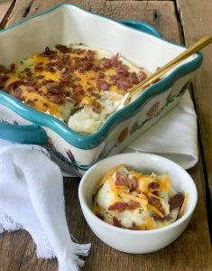 A small bowl of mashed cauliflower topped with bacon, cheese, and chives next to a larger square dish with the same cauliflower mash and toppings. Both dishes are sitting on a wooden background and white striped kitchen towel.