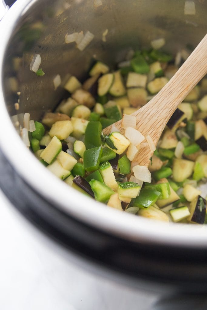Chopped zucchini, peppers, and onions being cooked in the Instant Pot with a wooden spoon resting on the side