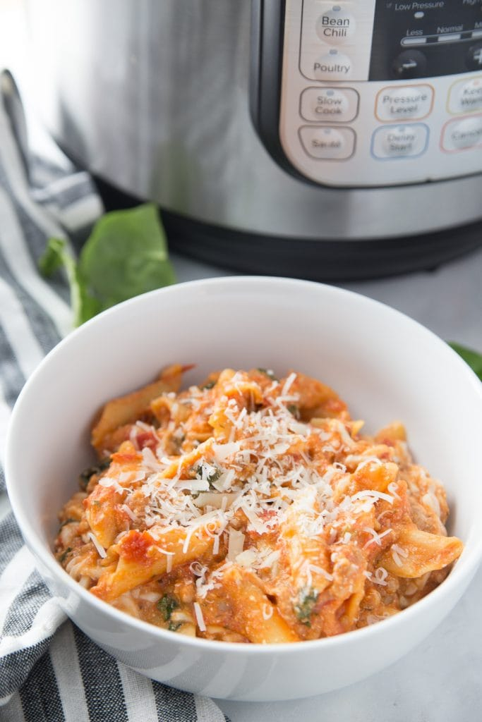 White bowl of bake ziti topped with cheese with an Instant Pot in the background