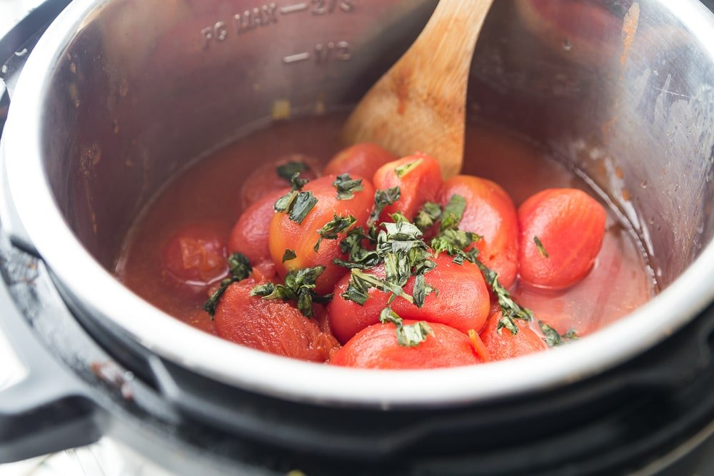 Instant Pot with whole San Marzano Plum Tomatoes and fresh basil