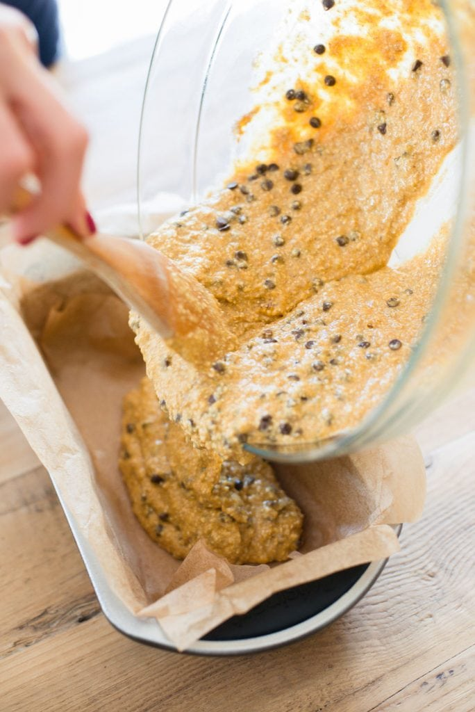 A woman's hand is shown using a wooden spoon to pour oatmeal banana pumpkin bread into a loaf pan lined with parchment paper.
