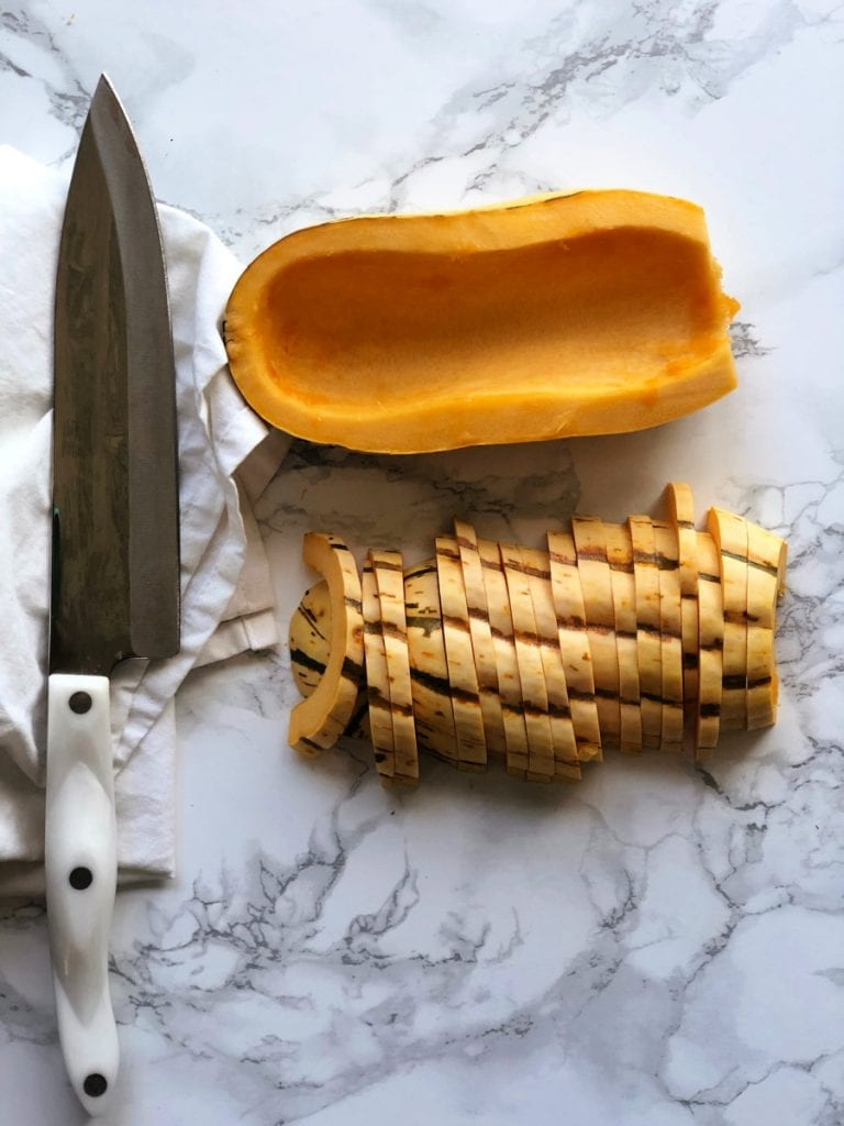 Sliced delicata squash on a marble countertop