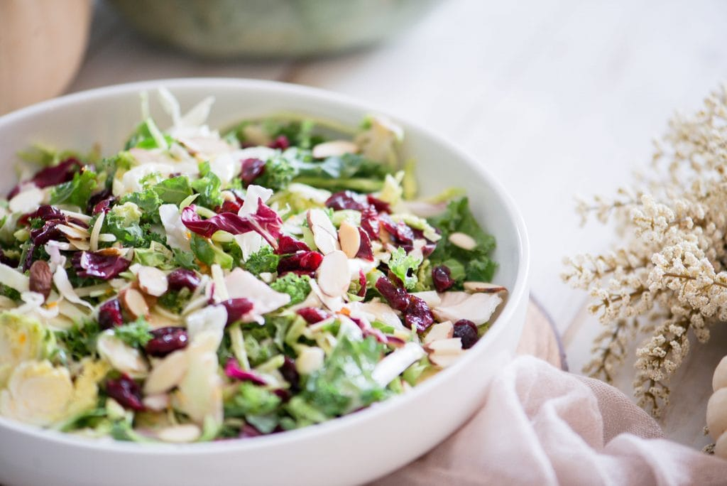 Close up side view of a bowl of festive Holiday Salad. The salad, made of purple cabbage, shaved Brussels sprouts, broccoli slaw, kale, and topped with dried cranberries and sliced almonds, is in a large white serving bowl. In the background is cream fall decor.