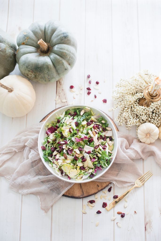 Overhead photo of Maple Cider Holiday Salad with festive fall decor. White, cream, and muted blue decorations surround the white serving bowl full of greens, dried cranberries, and sliced almonds.