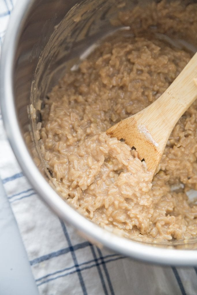 The inner lining of an instant pot with creamy delicious brown rice pudding being stirred with a wooden spoon.