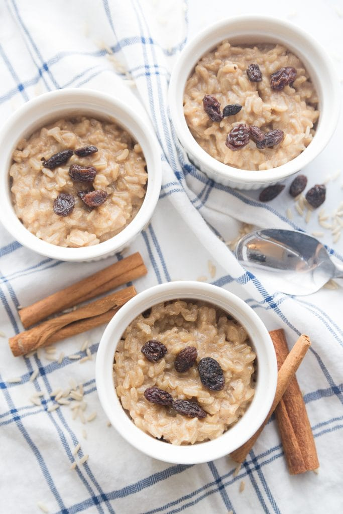 Three ramekins with healthy brown rice pudding, sitting on a blue and white cloth napkin. The rice pudding is topped with raisins and cinnamon, and cinnamon sticks sit nearby.