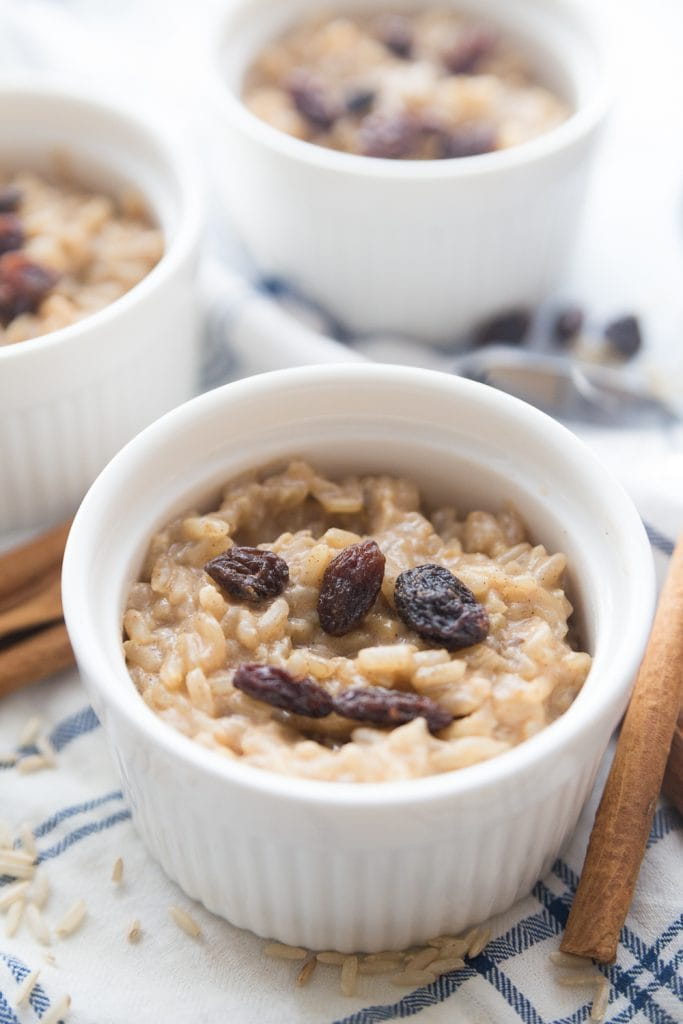 Close up of a small white ramekin with instant pot brown rice pudding topped with raisins.