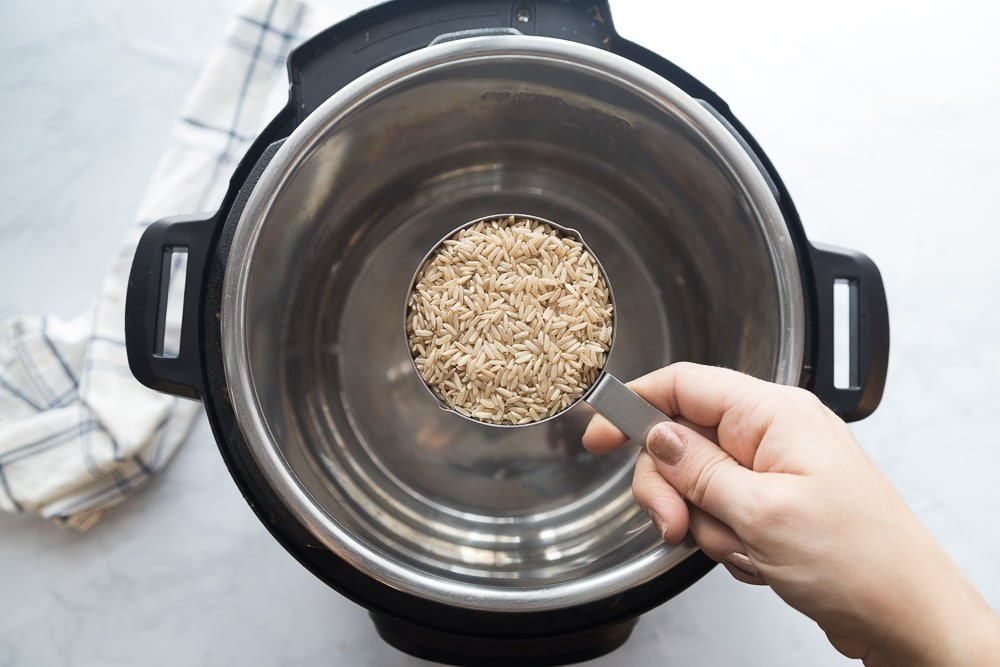 Overhead photo of Instant Pot with a measuring cup of rice