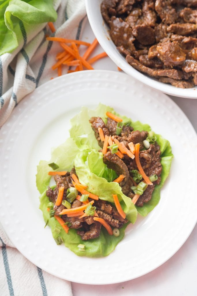 white plate with asian steak two lettuce wraps topped with matchstick carrots.