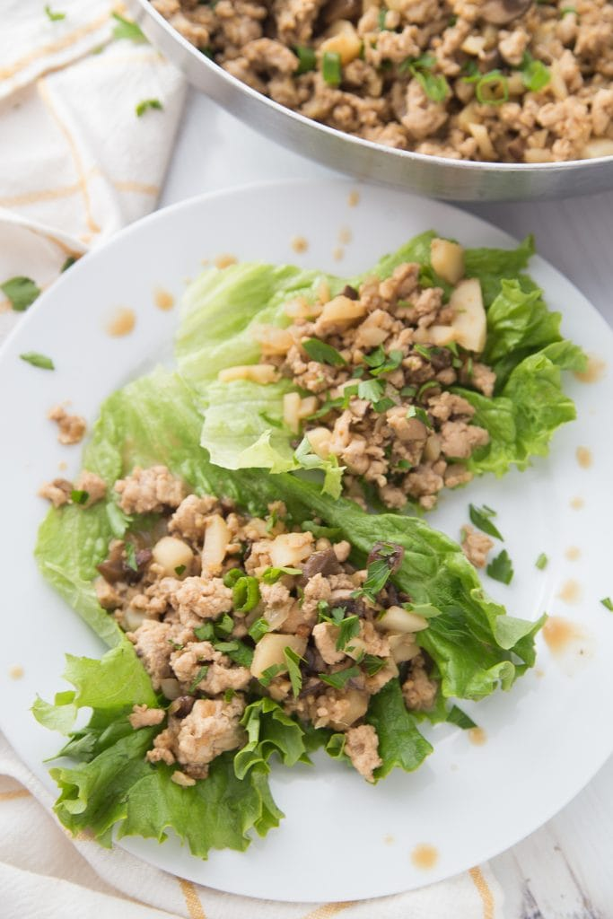 Ground chicken and veggie Lettuce wraps laying on a white plate with a pan of filling in the background