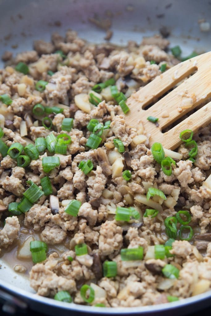 Ground chicken and veggies being sauteed in a pan with a slotted wooden spoon and garnished with green onions
