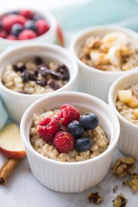 Four bowls of Instant Pot Steel Cut Oats with various fruit toppings