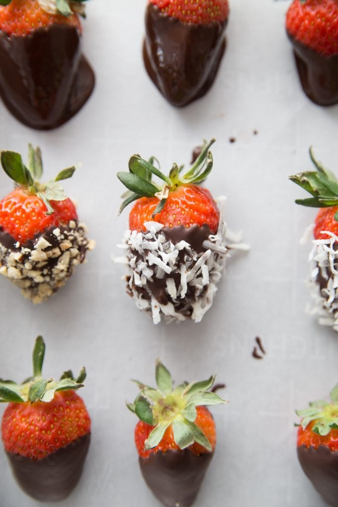 A lined baking sheet with chocolate covered strawberries - some with shredded coconut and some with chopped peanuts