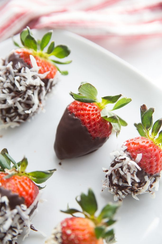 A plate of chocolate covered strawberries with various toppings