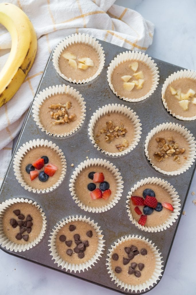 A cupcake tray lined with Healthy Blender Oatmeal Muffins with various toppings