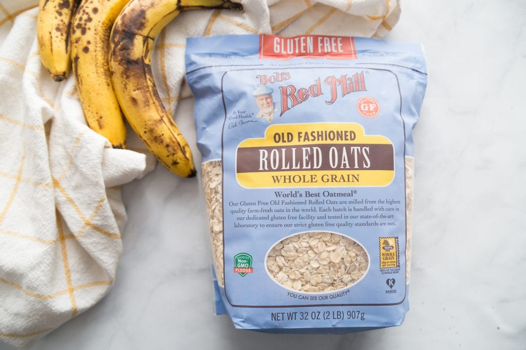 A bag of Bob's Red Mills Gluten Free Oats and three very ripe bananas sit on a white marble backround