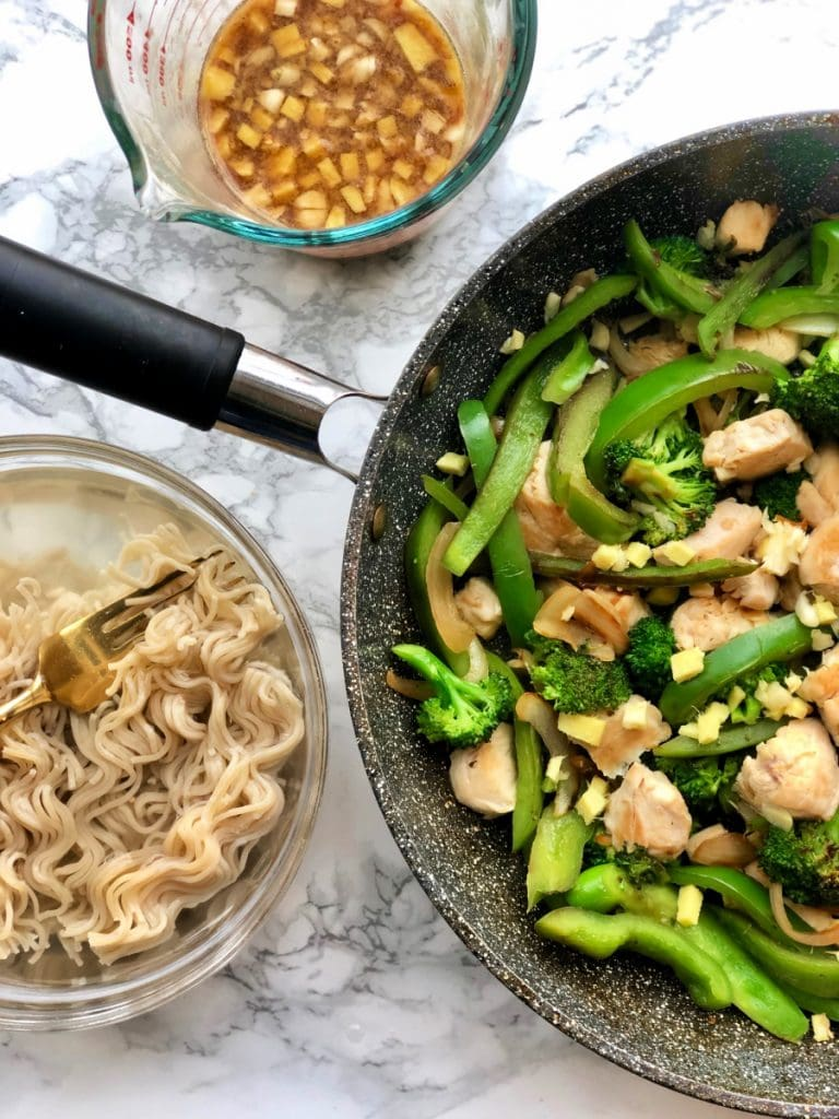 Brown Rice Ramen noodles sitting next to a skillet of chicken and veggies.