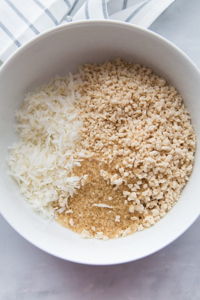 A bowl of gluten free panko, shredded coconut, and raw sugar awaits some coconut shrimp