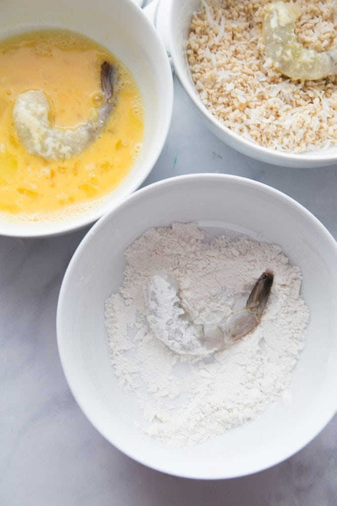 Three white bowls on a marble backdrop - one has egg with a shrimp, one has gluten free flour with shrimp, and one has panko breadcrumb with shrimp.