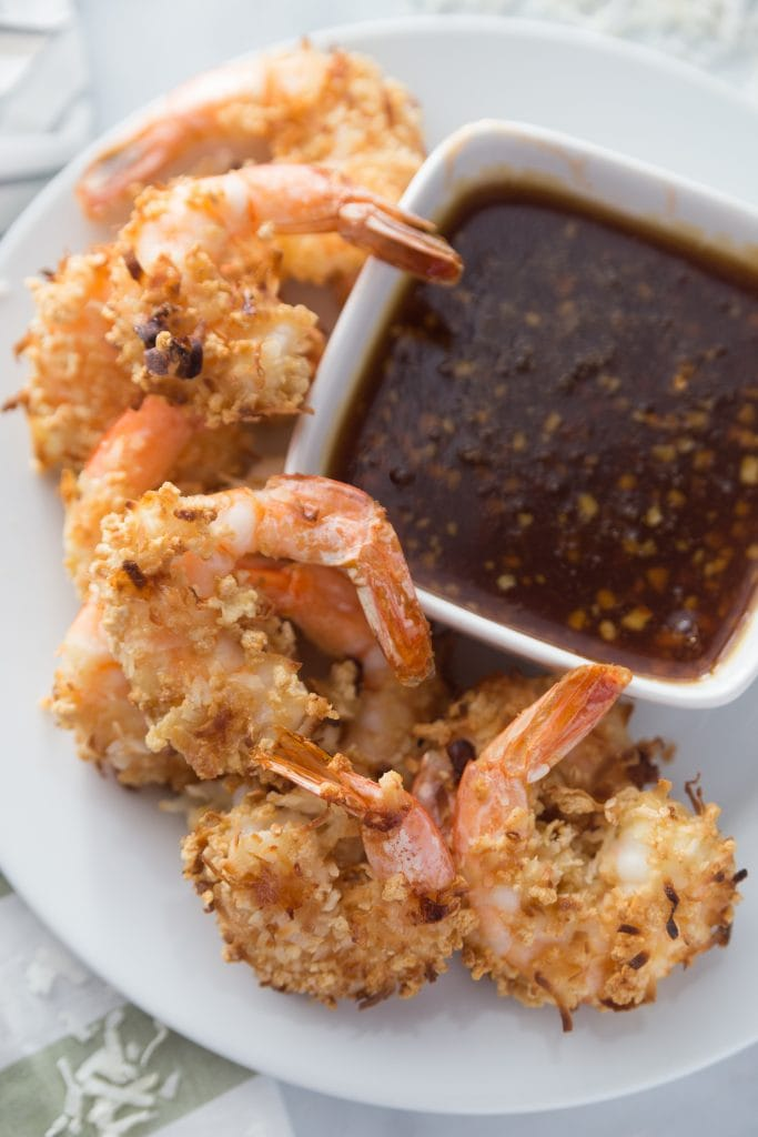 An overhead shot of several coconut shrimp sitting next to a bowl of homemade paleo sweet chili sauce