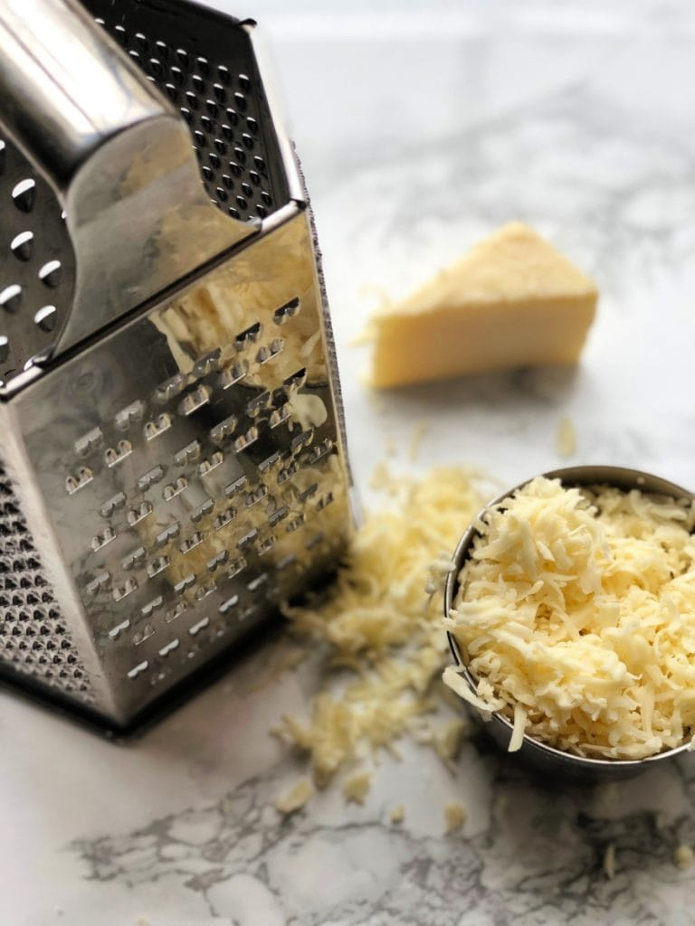 A box grater is sitting next to a cup of shredded cheddar on a marble background. A triangle piece of cheese sits behind.