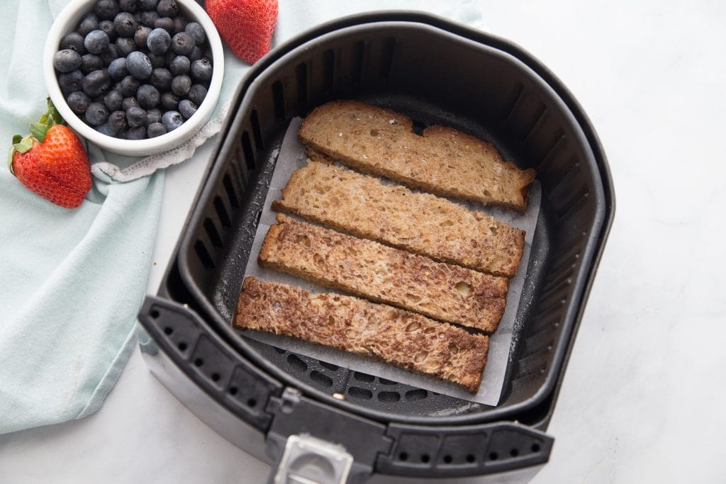 An airfryer basket lined with french toast sticks