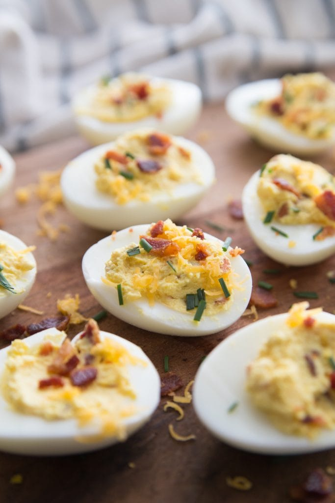 loaded deviled eggs topped with bacon and chives are placed randomly on a wooden cutting board- from a summer instant pot recipe round up on the blog confessions of a fit foodie