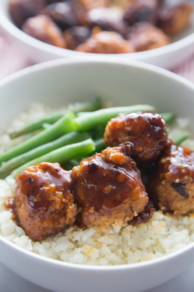 A close up shot of Asian Chicken Meatballs over a bowl of cauli rice