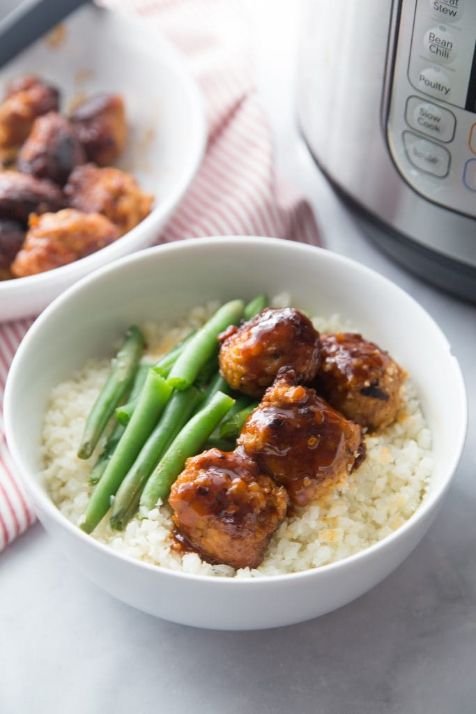 A bowl of Asian chicken meatballs over cauliflower rice