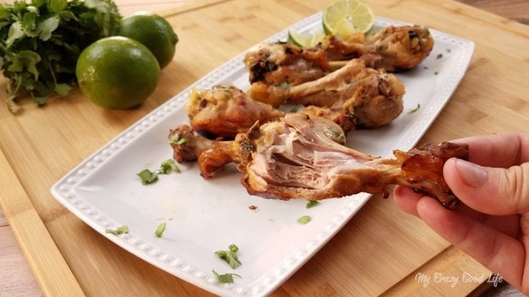 Cilantro Lime drumsticks are lined up on a rectangular serving tray. One is being held off camera and has a bite taken out of it. There are limes and cilantro on the side.