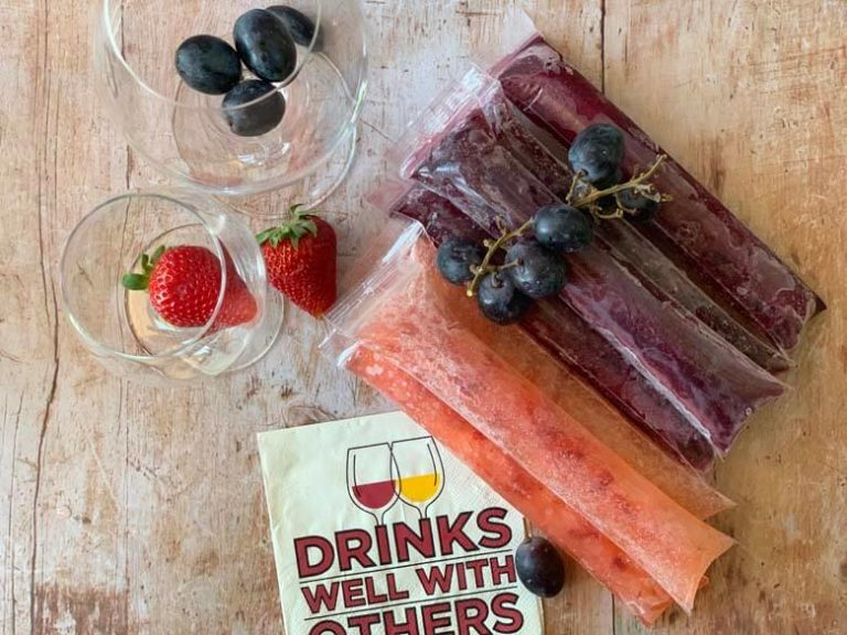 Two neat piles of wine popsicles are on a wooden surface and beginning to collect some frost. Wine glasses filled with fruit and cocktail napkins are nearby.