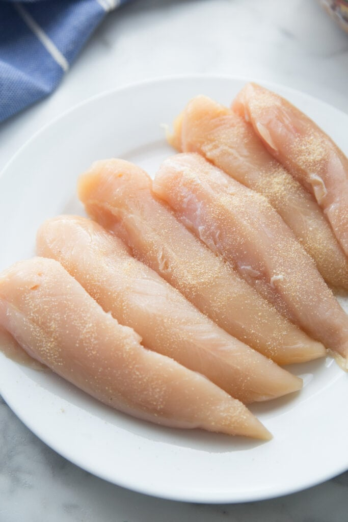 A white round plate of seasoned chicken tenderloins