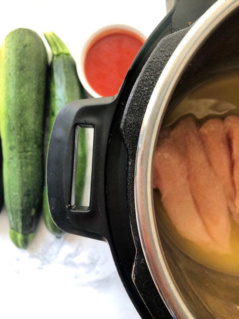 An Instant Pot with Zucchini and hot sauce nearby