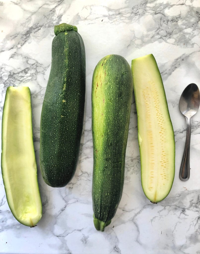 Zucchini being prepped for zucchini boats on a marble background