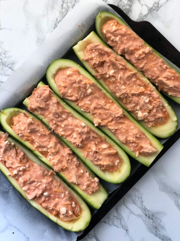 A baking sheet filled with Buffalo Chicken Zucchini Boats ready to go in the oven